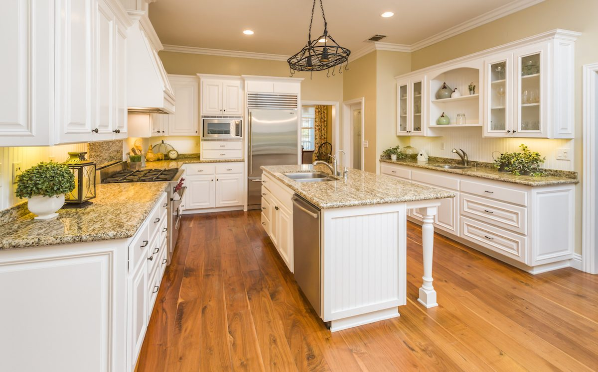 white kitchen cabinets stainless steel appliances granite countertops and hanging pot rack