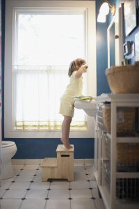 kid standing on a stool to reach the bathroom mirror